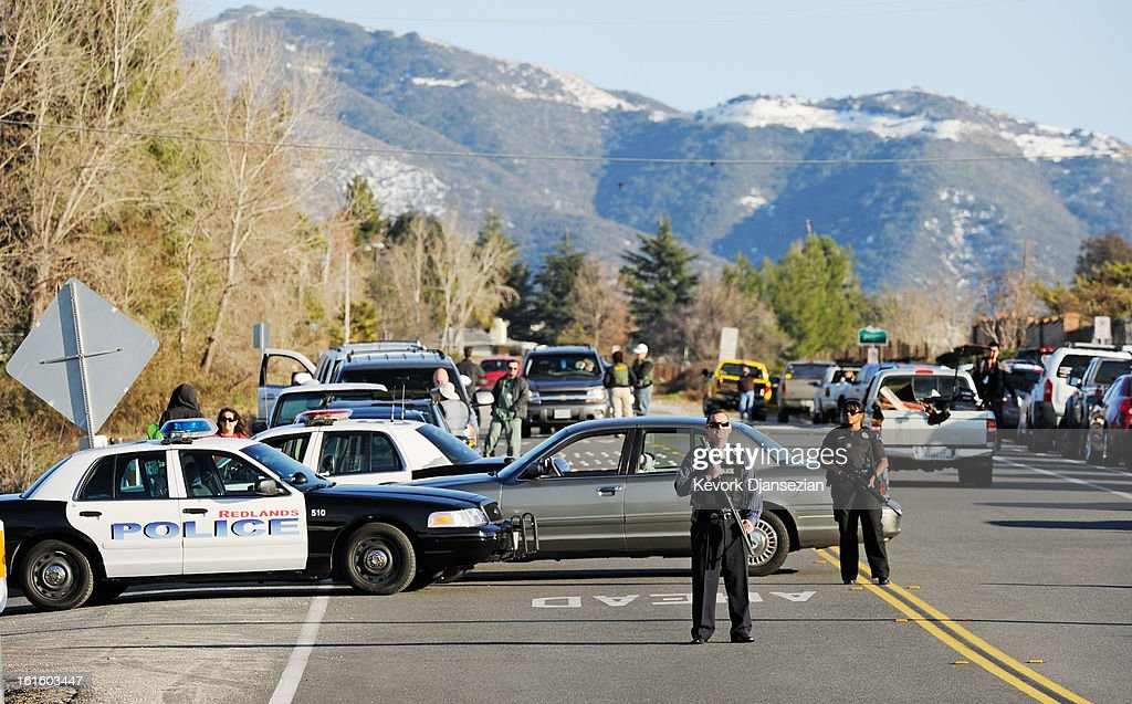 Redlands police officers at a blockade during a manhunt for the former Los Angeles Police Department officer Christopher Dormer who is suspected of triple murder on February 12, 2013 in Yucaipa, California. Dorner barricaded himself in a cabin near Big Bear, California and is in a standoff with authorities after shooting two police, killing one and wounding the other. Dorner, a former Los Angeles Police Department officer and Navy Reserve veteran, is wanted in connection with the deaths of an Irvine couple and a Riverside police officer.