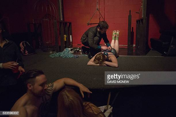 Redlines ties up voluntary submissive before suspending her at a dungeon party during the DomCon LA domination convention on May 21 2016 in Los...