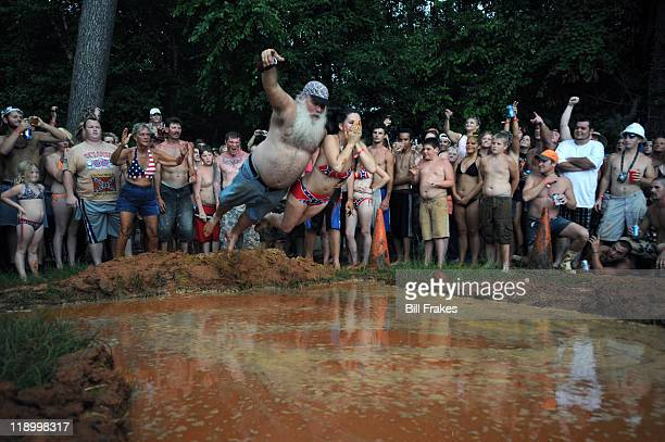 """16th Annual Summer Games: Robert """"Robo"""" Sprague and his wife Rawni diving during Mud Pit Belly Flop event at Buckeye Park. The Spragues married at..."""
