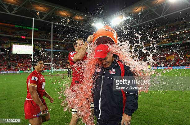 Reds coach Ewen McKenzie has a bucket of energy drink poured over him after winning the 2011 Super Rugby Grand Final match between the Reds and the...