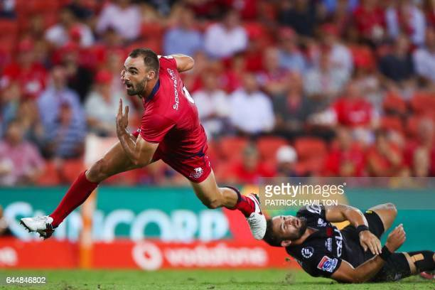 Reds' Nick Frisby evades a tackle by Sharks' Cobus Reinach during the Super Rugby match between the Reds and Sharks in Brisbane on February 24 2017 /...