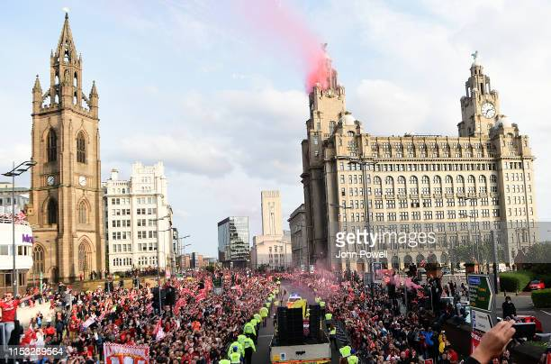Reds smoke rises from flares fired on top of the Liver Building as Liverpool fans watch the UEFA Champions League victory parade after their team won...
