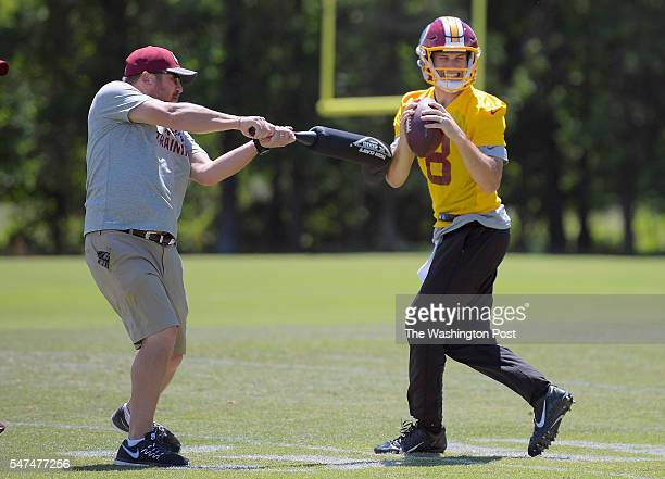Redskins had equipment manager Anders Beutel left uses a soft bat to sack at the ball in quarterback Kirk Cousins hands during the first day of the...
