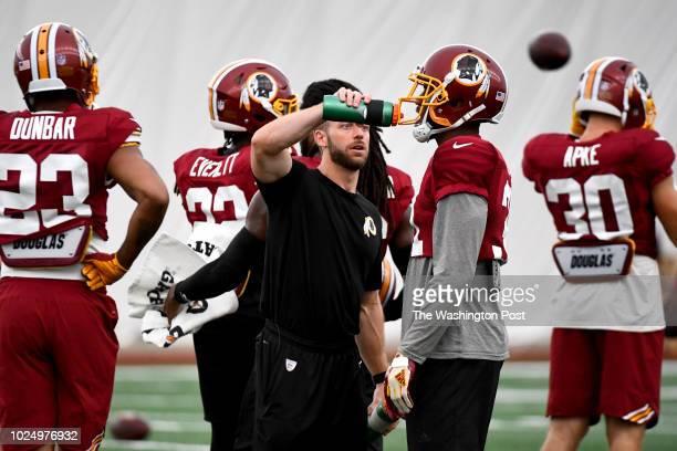 Redskins head nutritionist Jake Sankal makes sure Washington Redskins cornerback Fabian Moreau is hydrated during practice August 21 2018 in Ashburn...