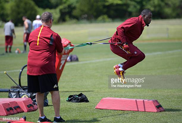 Redskins head trainer Larry Hess left works with rehabbing linebacker Junior Galette as the Washington Redskins conduct OTA's at Redskins Park in...