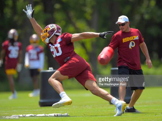Redskins linebacker Montez Sweat left blows by outside linebackers coach Chad Grimm during an OTA at Redskins Park in Ashburn VA on May 29 2019