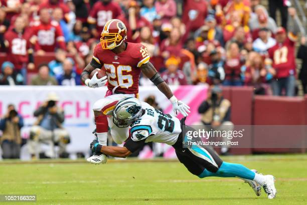Redskins running back Adrian Peterson is tackled by Carolina safety Eric Reid during the second quarter in a game against the Carolina Panthers and...