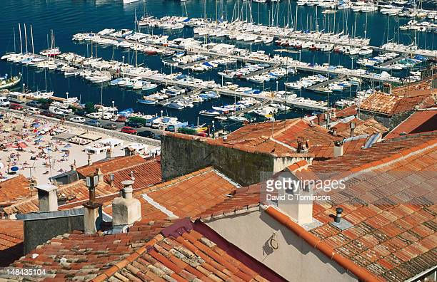 Red-tile roofs of houses in old town and boats in harbour beyond, Alpes-Maritimes.