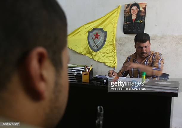 Redwan Mohammad Sharif the head of the Kurdish People's Protection Units' military conscription fills a book listing those who have served in the YPG...