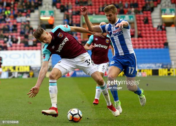 Reece Burke of West Ham United is challenged by Michael Jacobs of Wigan Athletic during The Emirates FA Cup Fourth Round match between Wigan Athletic...