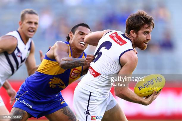 Reece Conca of the Dockers looks to break from a tackle by Jamaine Jones of the Eagles during the AFL Community Series match between the West Coast...
