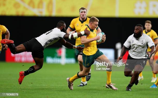 Reece Hodge of Australia is tackled by Semi Radradra of Fiji during the Rugby World Cup 2019 Group D game between Australia and Fiji at Sapporo Dome...