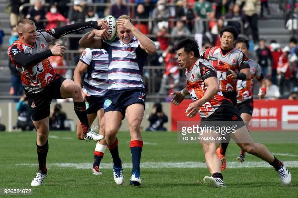 Reece Hodge of Rebels is tackled by Robbie Robinson and Ryota Nakamura of Sunwolves during their Super Rugby match between Japan's Sunwolves and...