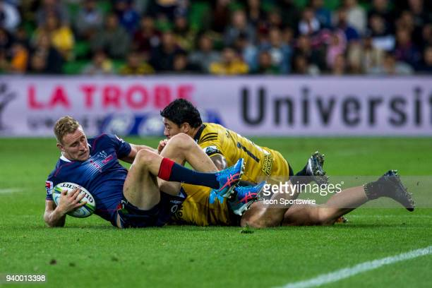 Reece Hodge of the Melbourne Rebels gets tackled by Ben Lam of the Wellington Hurricanes and another Wellington Hurricanes player during Round 7 of...