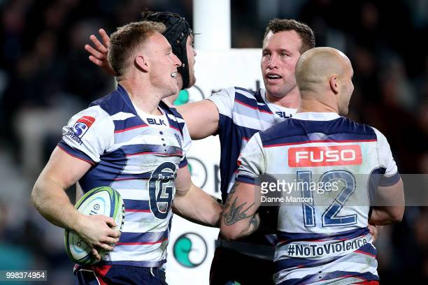 Reece Hodge of the Rebels celebrates his try with teammates during the round 19 Super Rugby match between the Highlanders and the Rebels at Forsyth...