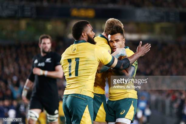 Reece Hodge of the Wallabies celebrates with teammates Will Genia and Marika Koroibete after scoring a try during The Rugby Championship game between...