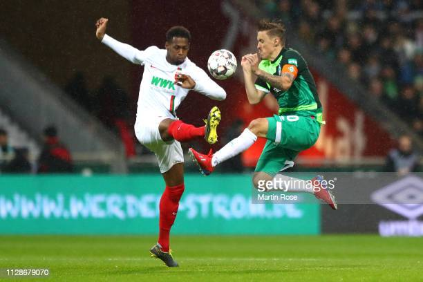 Reece Oxford of Augsburg balltles for the ball with Max Kruse auf Bremen during the Bundesliga match between SV Werder Bremen and FC Augsburg at...