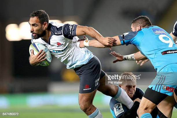Reece Robinson of the Waratahs is tackled by Bryn Hall of the Blues during the round 17 Super Rugby match between the Blues and the Waratahs at Eden...