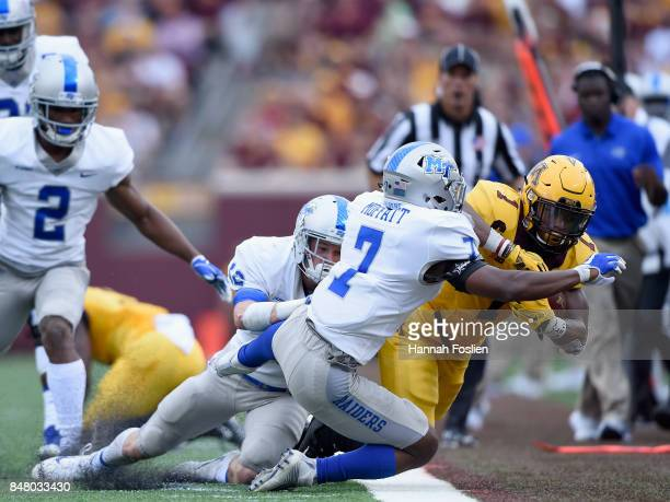 Reed Blankenship and Jovante Moffatt of the Middle Tennessee Raiders push Rodney Smith of the Minnesota Golden Gophers out of bounds during the...