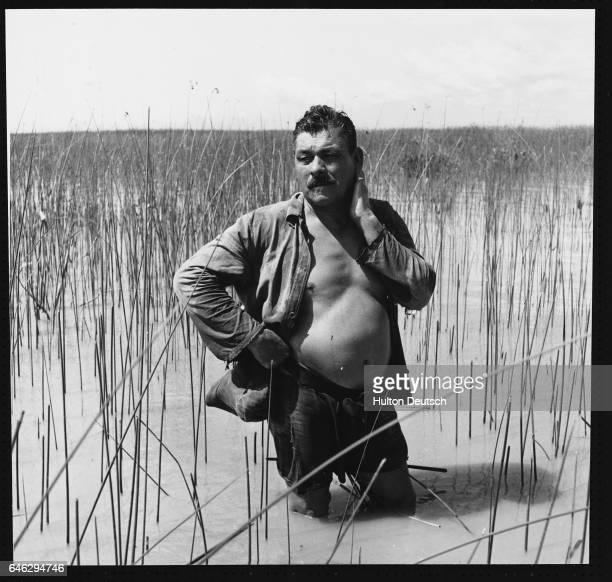 A reed cutter stands kneedeep in the waters of the Parana River delta