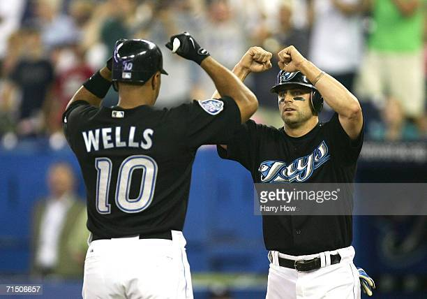 Reed Johnson of the Toronto Blue Jays greets Vernon Wells to celebrate his tworun home run in the first inning against the New York Yankees on July...