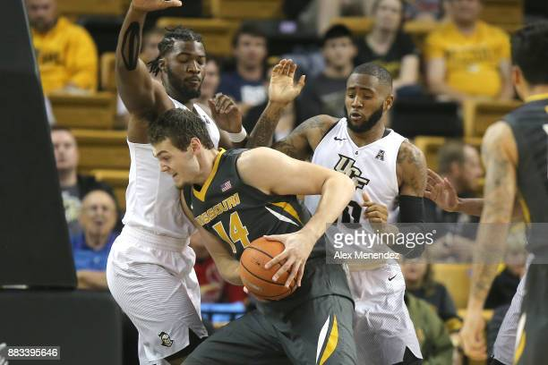 Reed Nikko of the Missouri Tigers drives to the basket against Chad Brown and Dayon Griffin of the UCF Knights during a NCAA basketball game at the...