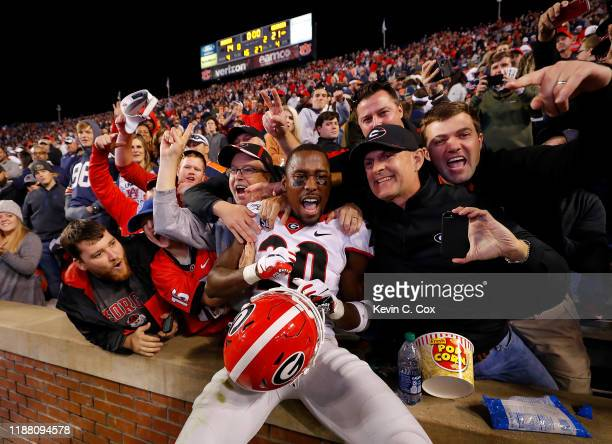 Reed of the Georgia Bulldogs celebrates their 21-14 win over the Auburn Tigers with fans at Jordan-Hare Stadium on November 16, 2019 in Auburn,...
