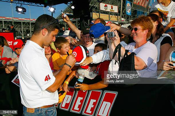 Reed Sorenson driver of the Target/Maxwell House Doge signs autographs for fans during a live broadcast of Trackside on the SPEED network on the...