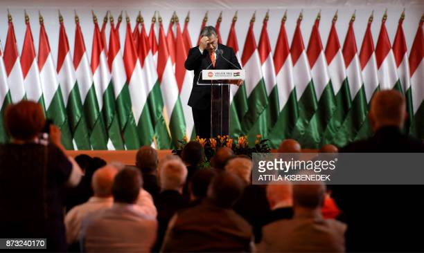 Reelected chairman of the governing FIDESZ party Hungarian Prime Minister Viktor Orban reacts as he speaks on the podium during the party congress at...