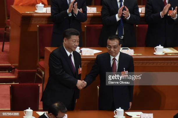 Reelected Chinese President Xi Jinping and Chinese Premier Li Keqiang shake hands after hearing the results of the election during the 5th plenary...