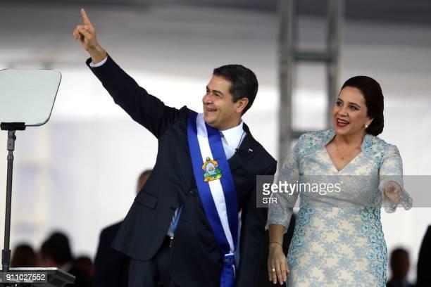 Reelected Honduran President Juan Orlando Hernandez waves at the crowd wearing the presidental sash next to First Lady Ana García at the Tiburcio...