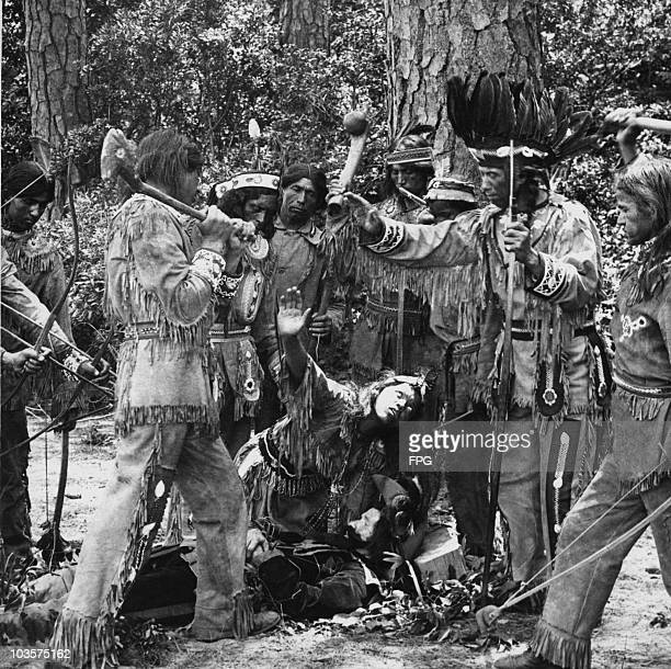 Reenactment depicting Pocahontas pleading for the life of John Smith with a group dressed as native Americans armed with bows and axes USA circa 1607...