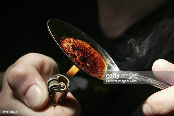 Reenactment of heroin user burning heroin on spoon Heroin is a narcotic drug which is also used for medical purposes as a strong painkiller Heroin is...