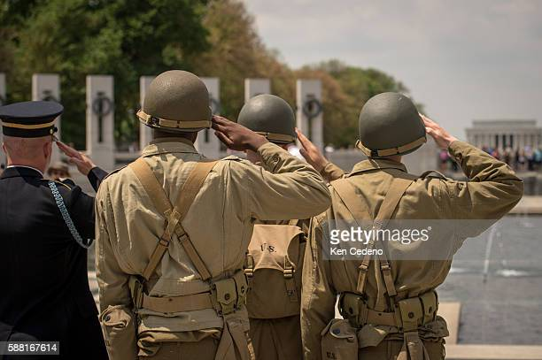 Reenactment soldiers from Ft Myer salutes as vintage WWII planes perform the missing man formation during a diverse array of World War II aircraft...