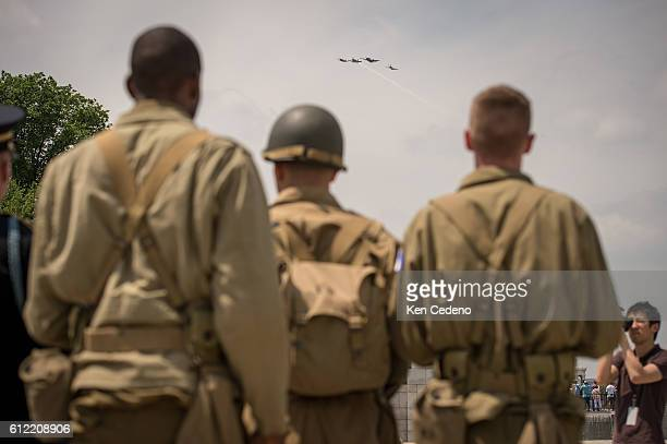 Reenactment soldiers from Ft Myer watch as vintage WWII planes perform the missing man formation during a diverse array of World War II aircraft ever...