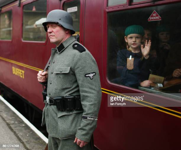 A reenactor dressed as a German Army soldier stands guard on the platform as a young girl looks from the carriage window during the North Yorkshire...