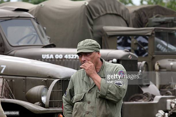 A reenactor dressed as a Second World War American soldier smokes a cigarette in front of vehicles being displayed as part of the twoday Maiden...