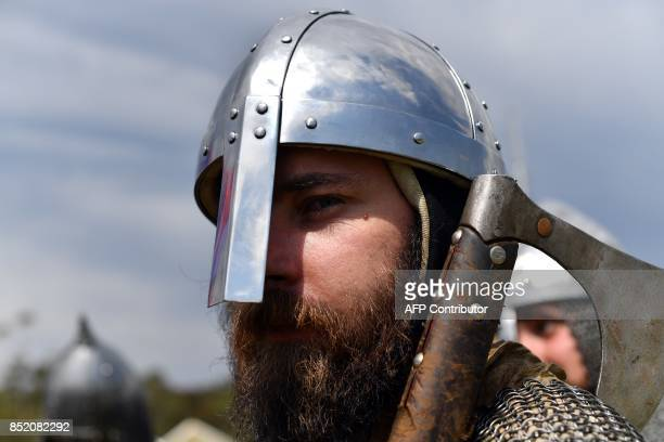 A reenactor dressed as a viking march toward the battle field for a mock fight at the St Ives Medieval Faire in Sydney on September 23 2017 / AFP...