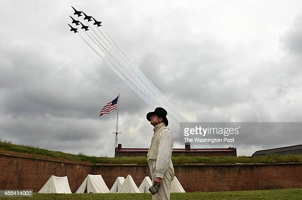 Reenactor Gary Schwartz of Silver Spring MD stands near an encampment as the Blue Angels fly overhead during the StarSpangled Spectacular Air Show...