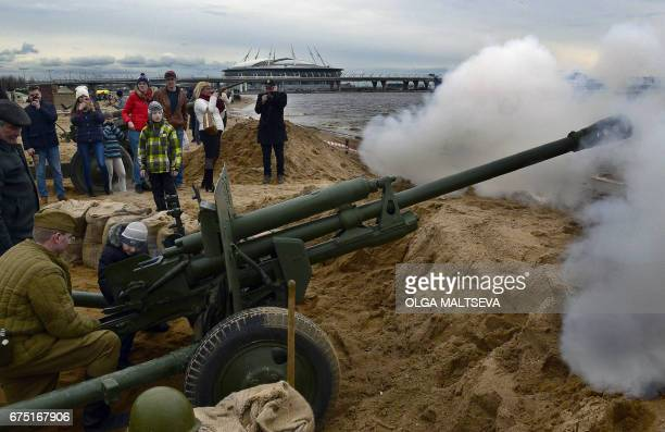 A reenactor helps a boy to fire from a historical artillery unit during a military historical festival with the new 'Saint Petersburg' football...