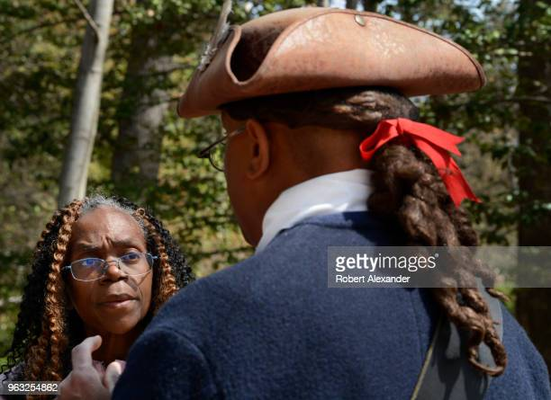 A reenactor in Colonial and Revolutionary War era clothing talks with tourists at Mount Vernon the plantation owned by George Washington in Fairfax...