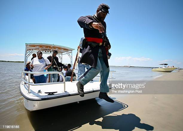 Reenactor Louis Carter with the 54th Regiment Massachusetts Volunteer Infantry leaps off a boat onto Morris Island for ceremonies to honor the...