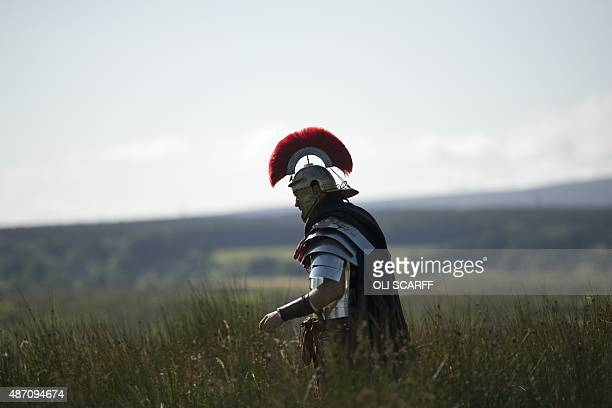 A reenactor portraying a soldier from the Imperial Roman Army prepares walks through long grass during English Heritage's history weekend Hadrians...