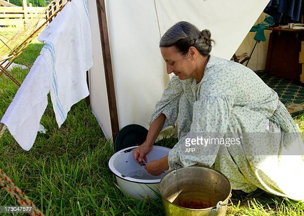 A reenactor washes breakfast dishes in the Confederate camp on July 5 2013 at the 150th Gettysburg celebration and reenactments in Gettysburg...