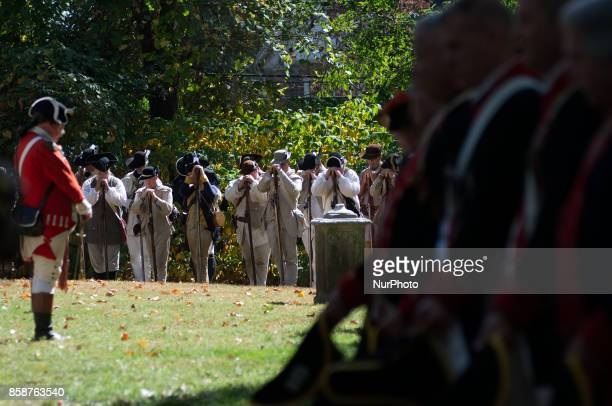 Reenactors bow heads during a ceremony as a moment of silence is held to commemorate recent events at the Revolutionary Germantown Festival at the...