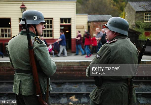 Reenactors dressed as German Army soldiers stand guard on the platform at Levisham Station during the North Yorkshire Moors Railway 1940's Wartime...