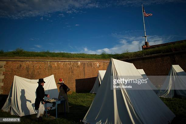 Reenactors Tom Salemi from Greenville North Carolina a War of 1812 infantryman and Julie Herczeg from Staunton Virginia a laundress talk in camp...