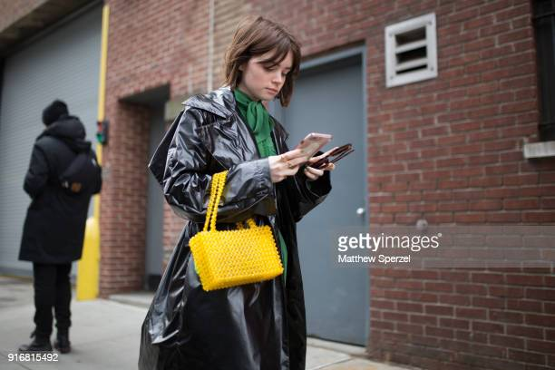 Reese Blutstein is seen on the street attending SelfPortrait during New York Fashion Week wearing a black vinyl coat with green dress on February 10...