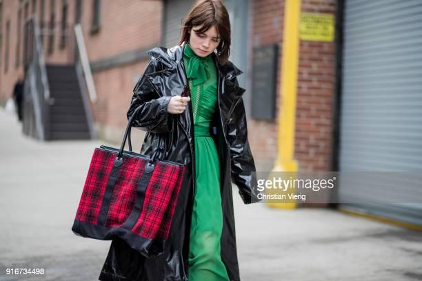 Reese Blutstein wearing green dress black vinyl coat checked bag ankle boots seen outside SelfPortrait on February 10 2018 in New York City