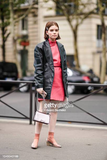 Reese Blutstein wears a black leather jacket a red dress a silver bag outside Miu Miu during Paris Fashion Week Womenswear Spring/Summer 2019 on...
